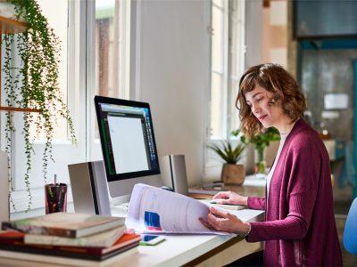 cô gái làm việc cùng tài liệu và máy tính